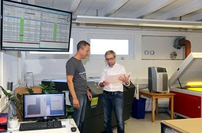 Prepress-Mitarbeiter Frank May (l.) und Geschäftsführer Holger Ostermann bei der Begutachtung der Druckplatten-Qualität