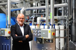 Herma-Geschäftsführer Dr. Thomas Baumgärtner vor der neuen dezentralen Dampferzeugungsanlage