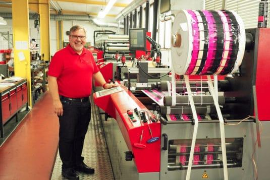 Dirk Handler, Geschäftsführer der Etikettenfabrik Küchler, neben einer seiner drei Codimag-Viva-Aniflo-420-Druckmaschinen