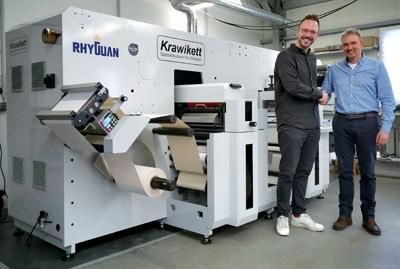 Krawikett-Geschäftsführer Benjamin Pose (l.) und Peer Boysen, Geschäftsführer B+T Tec, vor der neuen Rhyguan-Maschine (Quelle: B+T Tec)