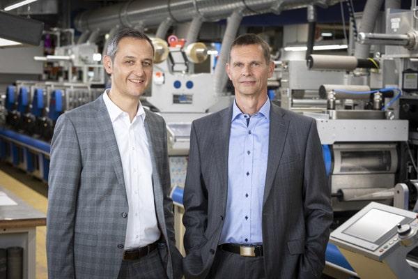 Die Carini-Geschäftsleitung vor einer der Druckmaschinen: Edgar Sohm (l.) MBA und Dr.-Ing. Harald Raak (Quelle: Carini)