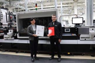 Yuan Li, aus dem Team der Vorstufentechnik am Fogra-Forschungsinstitut für Medientechnologien e.V. überreicht das Fogra-Zertifikat an Colour Consultant, Jochen Schäffner, von Canon Production Printing (Quelle: Canon)