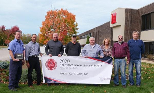 Jon Bauch (dritter von links) und das Sicherheitskomitee von Martin Automatic zeigen stolz die Plakette und das Banner des Dale Sabers Safety Award 2020 (Quelle: Martin Automatic)