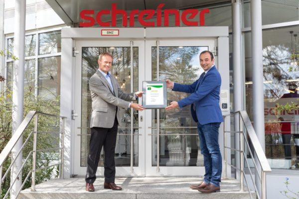 Oberschleißheims Bürgermeister Markus Böck freut sich, die Urkunde für den Umwelt- und Klimapakt Bayern an den Leiter des Umweltschutzmanagements bei der Schreiner Group, Dr. Thomas Gulden, zu übergeben (Quelle: Schreiner Group)