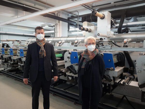 Brigitte Alers, Geschäftsführerin von bentlage-label GmbH (rechts) mit Michael Koch von Heidelberg Deutschland (links) vor der im Dezember 2020 installierten Gallus ECS 340, die die Kapazität und das Produktportfolio erweitert (Quelle: Gallus)