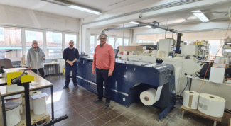 Geschäftsführer Ronald Kuhls (r.) zusammen mit Mitarbeitern vor der neuen AccurioLabel 230 (Quelle: ITA Systeme)
